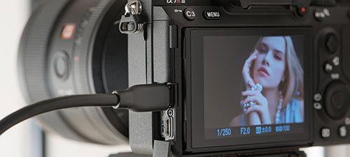 Port USB Type-C® zgodny ze standardem SuperSpeed USB 5Gb/s (USB 3.2) ułatwia przesyłanie do komputera dużych plików zdanymi wformacie RAW, dzięki czemu można szybko przeglądać obrazy na komputerze ibezzwłocznie kontynuować zdjęcia. Również ustawienie umożliwiające przesyłanie wyłącznie plików JPEG do komputera umożliwia szybsze sprawdzanie zdjęć przy użyciu komputera po fotografowaniu w trybie ciągłym, ponieważ aparat nie musi wysyłać dużych ilości danych w formacie RAW.